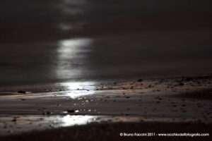 Riflesso delle onde sulla riva in notturna